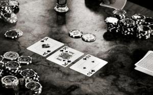 Svartvit bild med tre spelkort och spelmarker