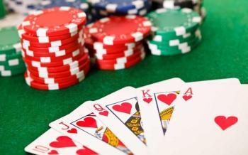 Tre högar med röda och gröna spelmarker samt en royal straight flush i hjärter på ett spelbord.